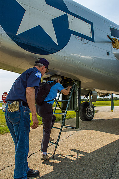 "A crew member of the ""Maid in the Shade"" helps Chris as she climbs into the belly of the B-25 Mitchell bomber."